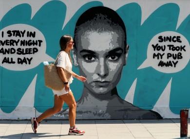 A woman walks past Irish artist Emmalene Blake's mural of singer Sinead O'Connor near the site of the old Bernard Shaw pub in Dublin.