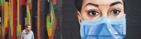A man looks at a mural showing a nurse wearing wearing PPE in London yesterday.