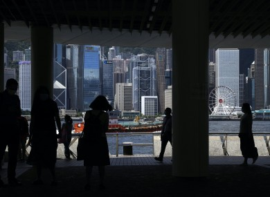 People walk along the waterfront of Victoria Harbour in Hong Kong