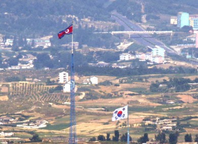Flags of North Korea, rear, and South Korea, front, flutter in the wind respectively at border area