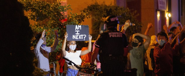 A demonstrator holds a sign up to a police officer during a protest in Washington DC.