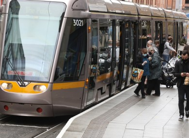 Passengers wearing masks enter and exit the Luas
