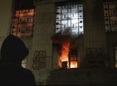 A protester watches as a mall fire burns in the entrance of the Alameda County Courthouse