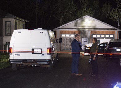 Investigators in a driveway at a house where the body of Martin Carpentier was found