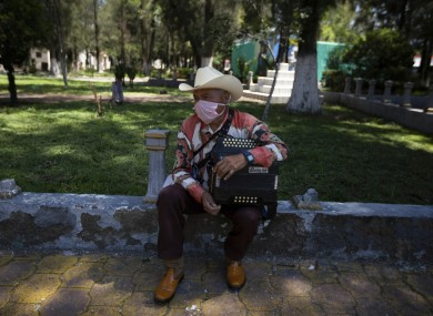 A musician waits for clients to hire him to serenade mourners during burial services on the outskirts of Mexico City.