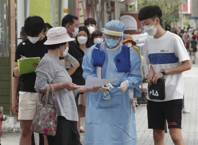 A medical worker guides people during the Covid-19 testing at a makeshift clinic in Seoul
