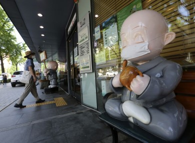 A Buddhist monk doll wearing a face mask is displayed near the Chogyesa temple in Seoul