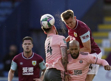 Jimmy Dunne of Burnley wins an aerial battle with Sheffield United's Oliver Burke and David McGoldrick.
