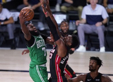 Boston Celtics' Jaylen Brown goes up for a shot as Miami Heat's Bam Adebayo and Jimmy Butler defend.