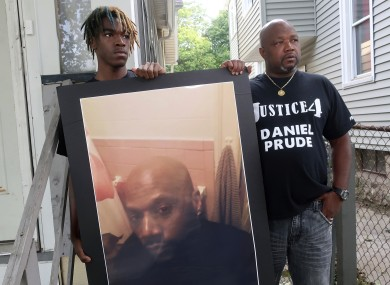 Joe Prude, uncle of Daniel Prude, right, and Daniel's nephew Armin, stand with a picture of Daniel Prude in Rochester New York yesterday.