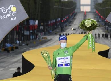 Sam Bennett of Ireland, wearing the best sprinter's green jersey, celebrates on the podium in Paris.