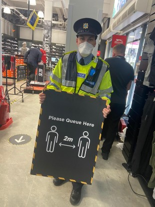 Image of garda member holding up a social distancing sign for a queue.