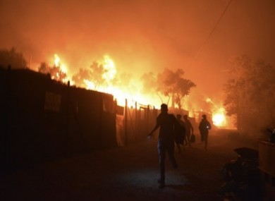 People flee from the fire as it burns through the Moria camp.
