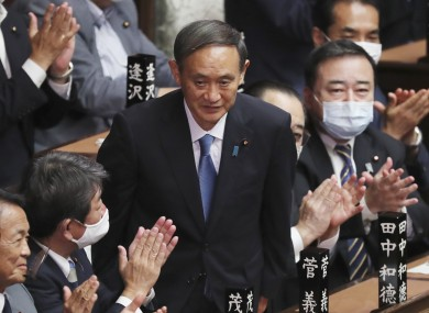 Yoshihide Suga stands up after being elected as Japan's new prime minister today.