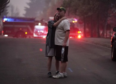 A couple embrace while touring in an area devastated by the Almeda Fire.