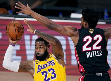 Los Angeles Lakers' LeBron James looks to pass while pressured by Miami Heat's Jimmy Butler.