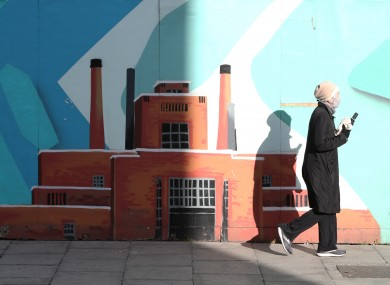 A woman wearing a face mask passes the Guinness mural on Thomas Street in The Liberties.