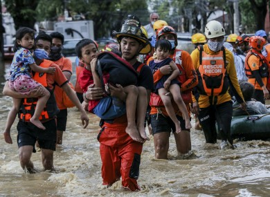 Rescuers carry children out from a flooded street due to heavy rains brought by Typhoon Vamco