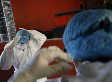 Doctors put on PPE as they prepare to conduct a Covid-19 test at a home in Mexico City