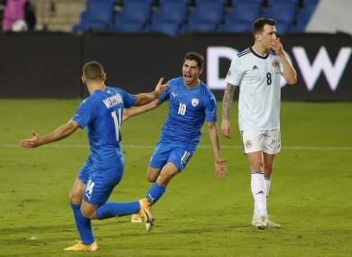Shon Weissman and Dia Seba celebrate after Israel's goal as Scotland's Ryan Jack looks dejected.