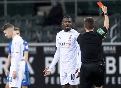 Referee Frank Willenborg shows Moenchengladbach's Marcus Thuram the red card.