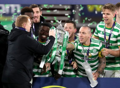 Celtic manager Neil Lennon takes the trophy from Scott Brown (right).