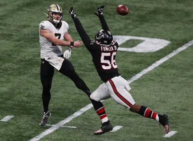 Taysom Hill gets off a pass under pressure from Atlanta Falcons defensive end Dante Fowler.