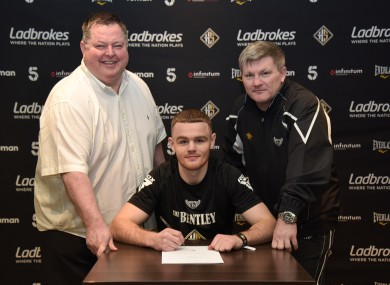 Brett McGinty signs his first professional deal with Mick Hennessy (L), as observed by trainer Ricky Hatton.