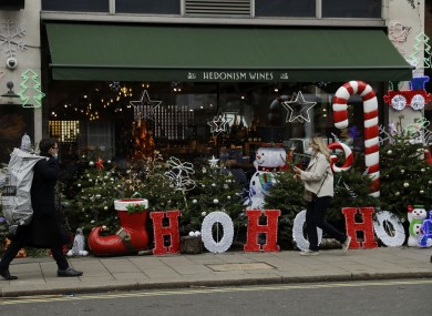 People walking past a decorated shop in London yesterday.
