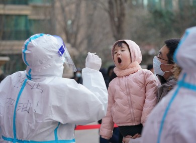 A medical worker collects a swab sample from a girl at a community in Qiaoxi District of Shijiazhuang