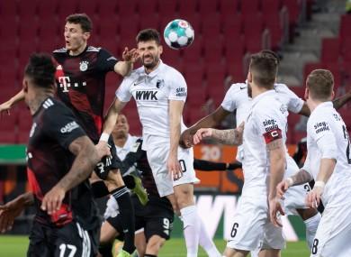 Bayern Munich's Benjamin Pavard and Daniel Caligiuri of Augsburg contesting for the ball.