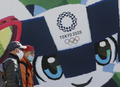 People walk by posters to promote the Tokyo 2020 Olympics on Tuesday.
