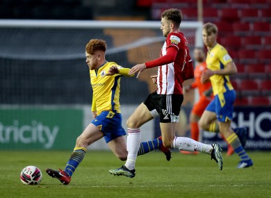 Aodh Dervin of Longford, tackled by Will Patching of Derry.