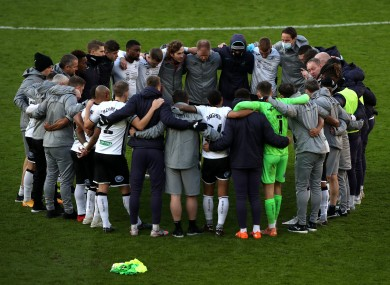 Swansea City players and staff in a huddle in the aftermath of a recent Championship fixture.