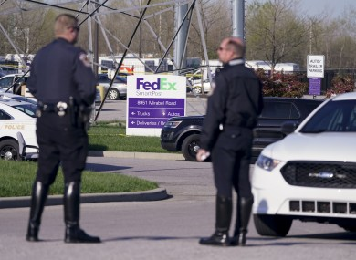 Police stand near the scene where multiple people were shot at the FedEx Ground facility early this morning.