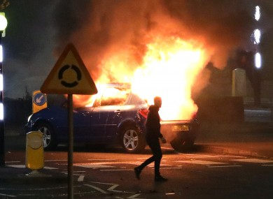 A car hijacked by loyalists protesters burns in Newtownabbey