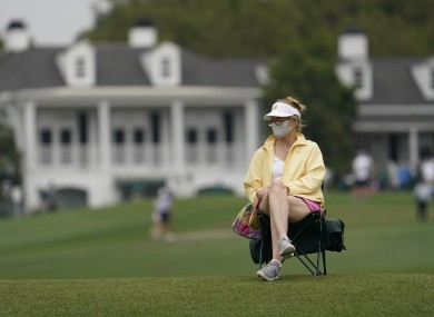 A masked spectator watches on at Augusta.