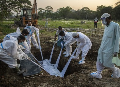 Municipal workers in protective suits bury the body of a person who died due to Covid-19 in Gauhati, India,
