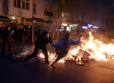 Police and participants clash during a fire at the edge of the demonstration in Berlin.