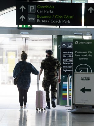 A member of the Irish Defence Forces escorting a person to Mandatory Hotel Quarantine