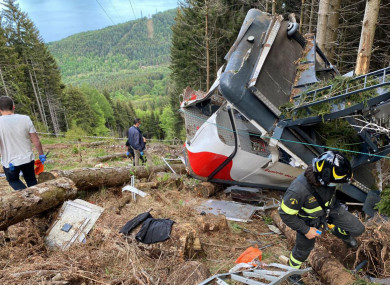 Rescuers work by the wreckage of a cable car after it falls in north Italy's Piedmont region.