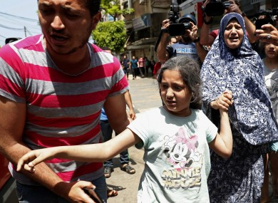 A man helps a wounded girl and a woman to an ambulance after an Israeli airstrikes at their building in Gaza City today.