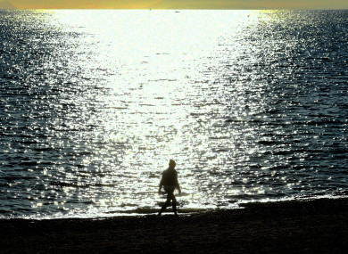 A woman walks on the beach in Marbella, Andalusia.
