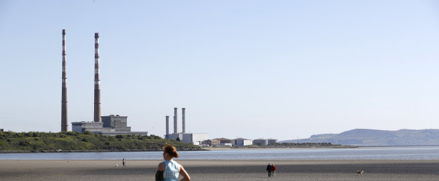 People enjoy sunny weather on Sandymount strand with by the Poolbeg chimney stacks in the background.