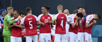 Denmark players make a wall around teammate Christian Eriksen being assisted by medics.