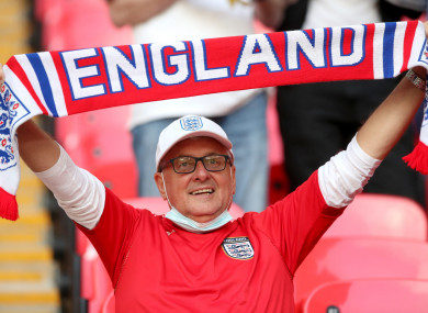An England fan holding a scarf in the stands at Wembley Stadium.