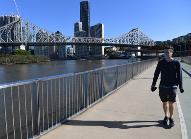 A man wearing a protective face mask is seen walking on the New Farm riverwalk, beside the Brisbane River in Brisbane