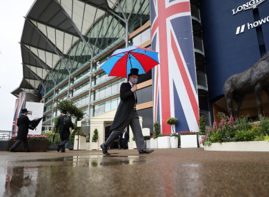 Racegoers carrying umbrellas arrive for day four of Royal Ascot at Ascot Racecourse.