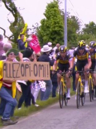 A fan holds a sign into which Tony Martin crashed, causing half of the peloton to tumble with him.