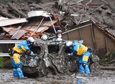 Rescuers check a damaged vehicle at the site of a mudslide in Atami, Shizuoka prefecture, southwest of Tokyo